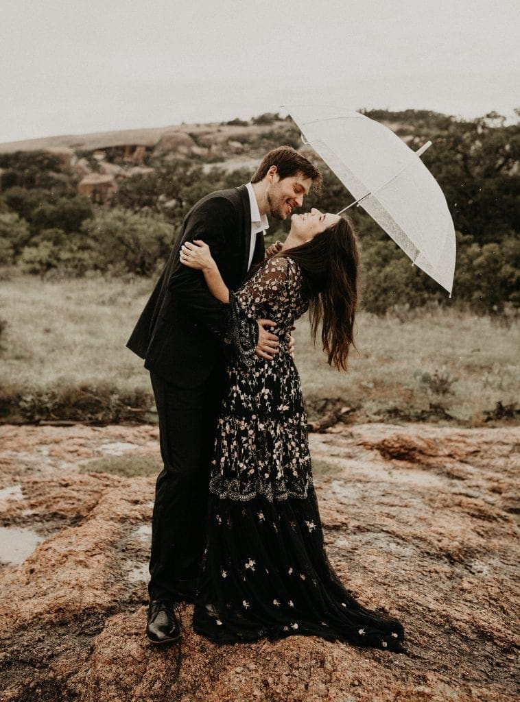 Bride to be and groom to be embrace while bride to be holds an umbrella and is laughing while the groom to be leans in for a kiss at Enchanted Rock, Texas. Photograph by Austin, Texas wedding photographer Nikk Nguyen.