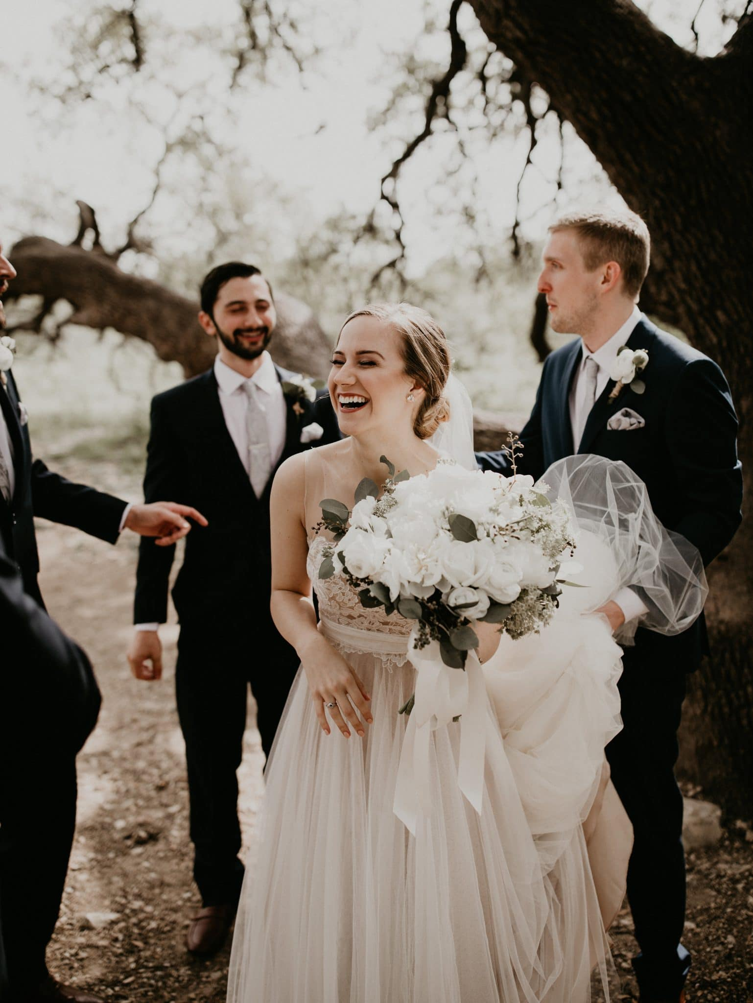 Bride holding her bouquet and laughing in front of a tree with the groom holding the train of her dress and the groomsmen around them at the Brodie Homestead in Sunset Valley, Texas. Photograph by Austin, Texas wedding photographer Nikk Nguyen.