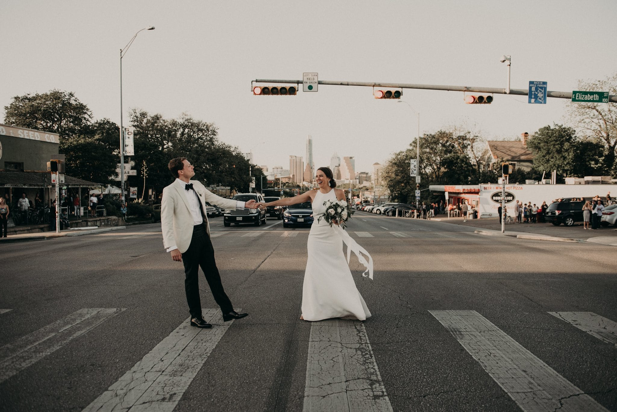 Bride holding her bouquet and holding hands and dancing with the groom in the crosswalk of the street of downtown Austin, Texas. Photograph by Austin, Texas wedding photographer Nikk Nguyen.