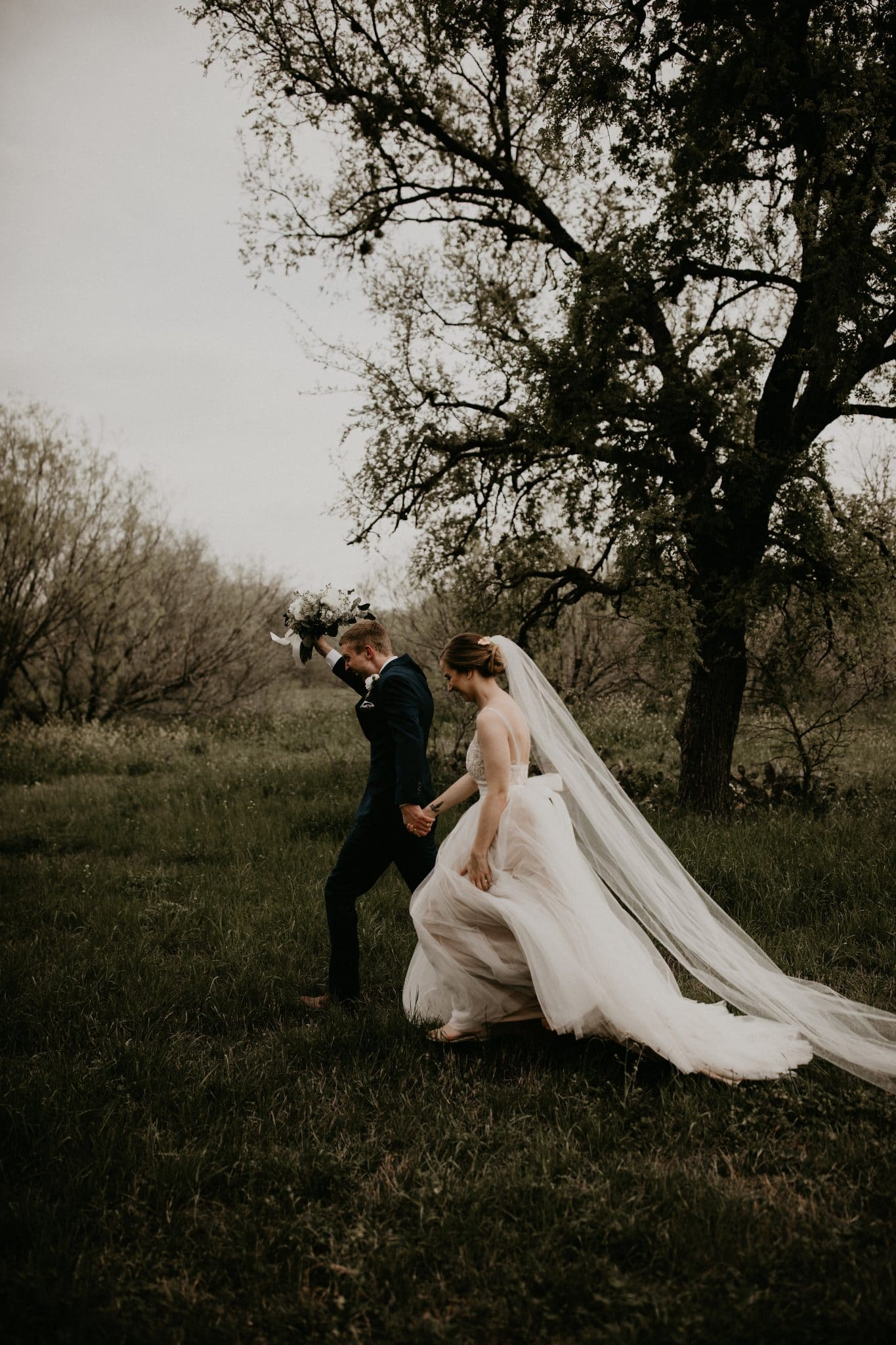 Groom holding bride's bouquet in the air as if celebrating as he walks away holding the brides hand in the grass of the Brodie Homestead in Sunset Valley, Texas. Photograph by Austin, Texas wedding photographer Nikk Nguyen.