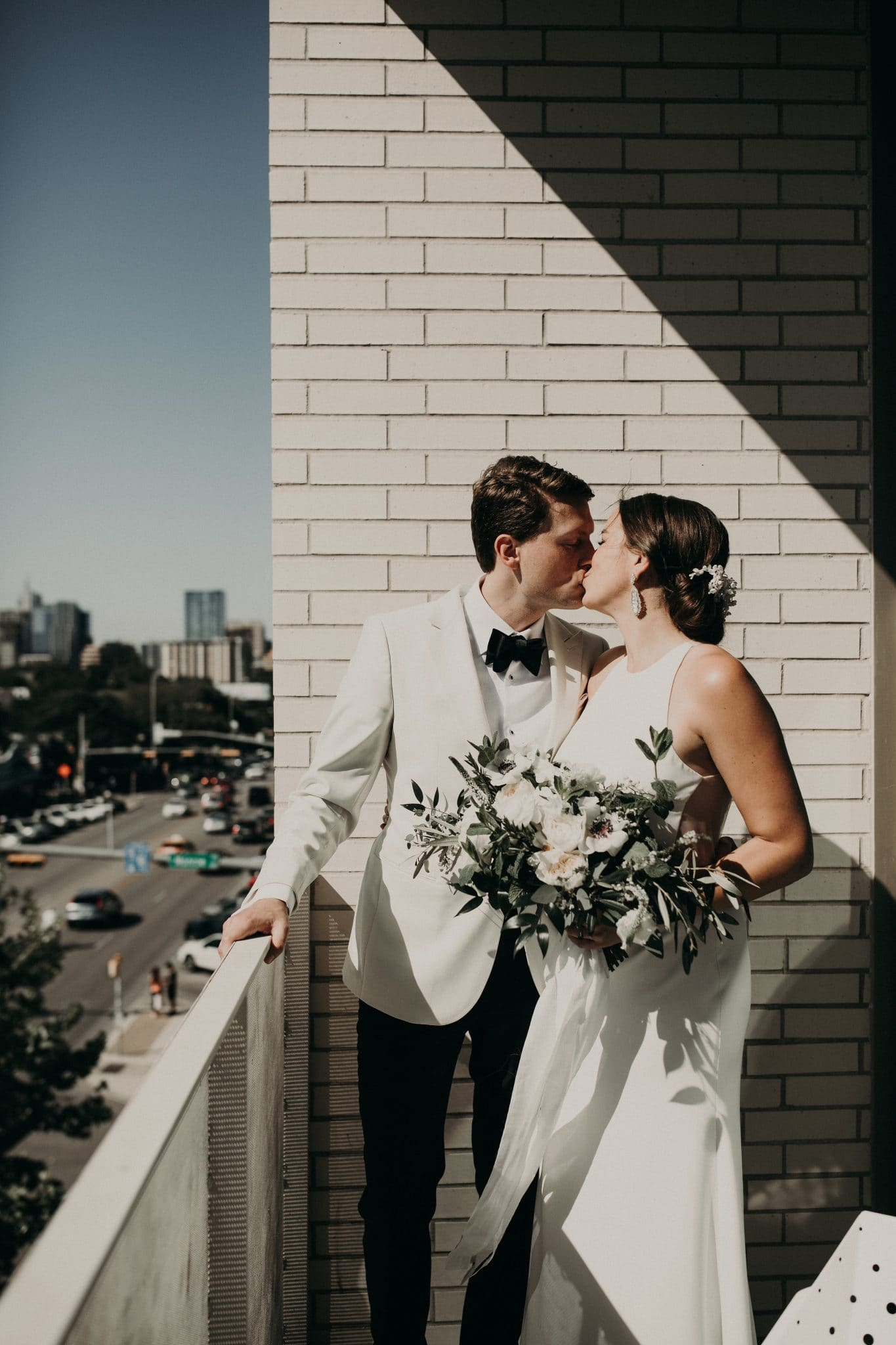 Bride holding her bouquet as she kisses the groom while standing on a balcony in downtown Austin, Texas. Photograph by Austin, Texas wedding photographer Nikk Nguyen.