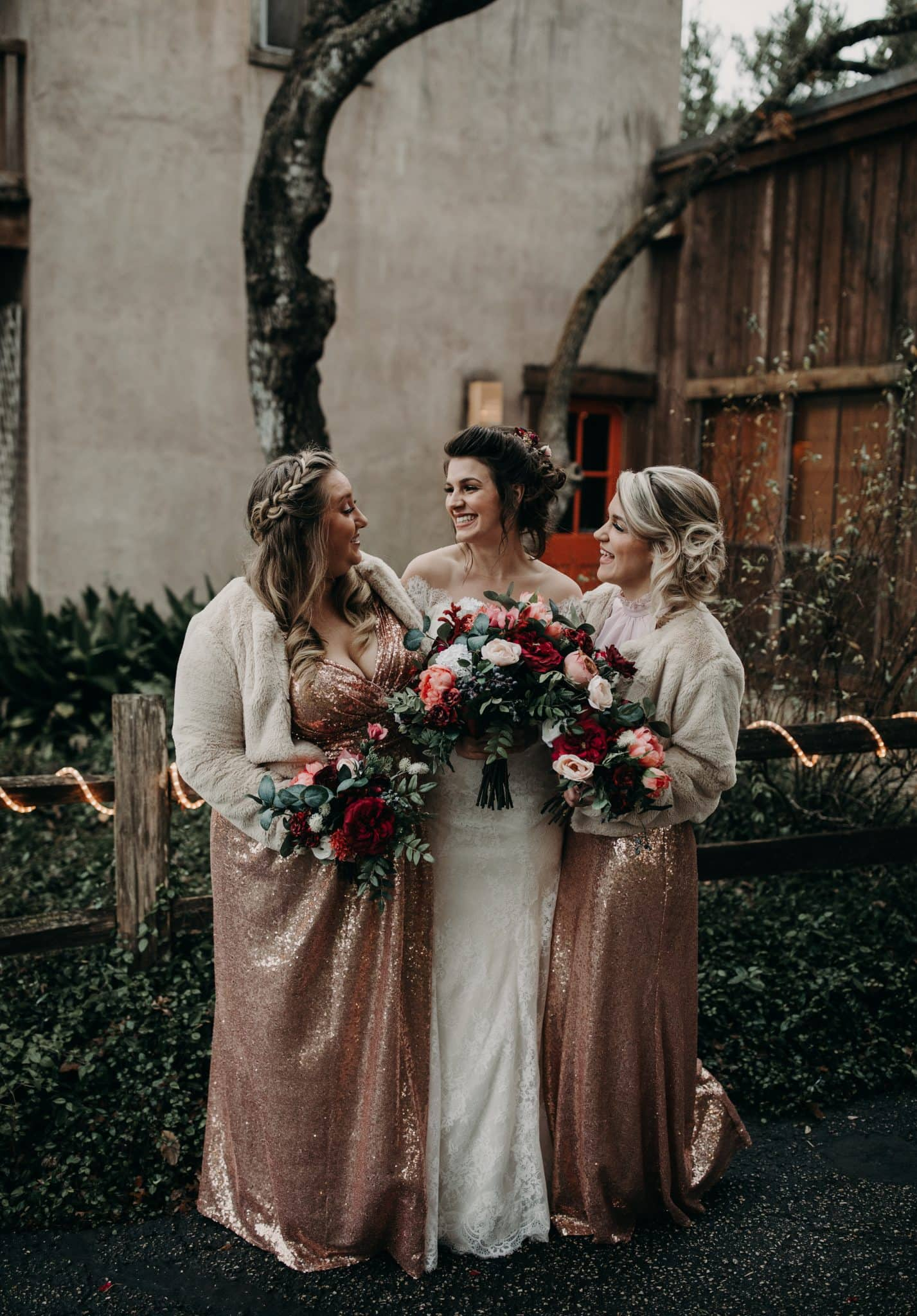 Bride and her 2 bridesmaid in sequin dresses holding their bouquets and smiling at each other on the lawn of the House on the Hill in Austin, Texas. Photograph by Austin, Texas wedding photographer Nikk Nguyen.