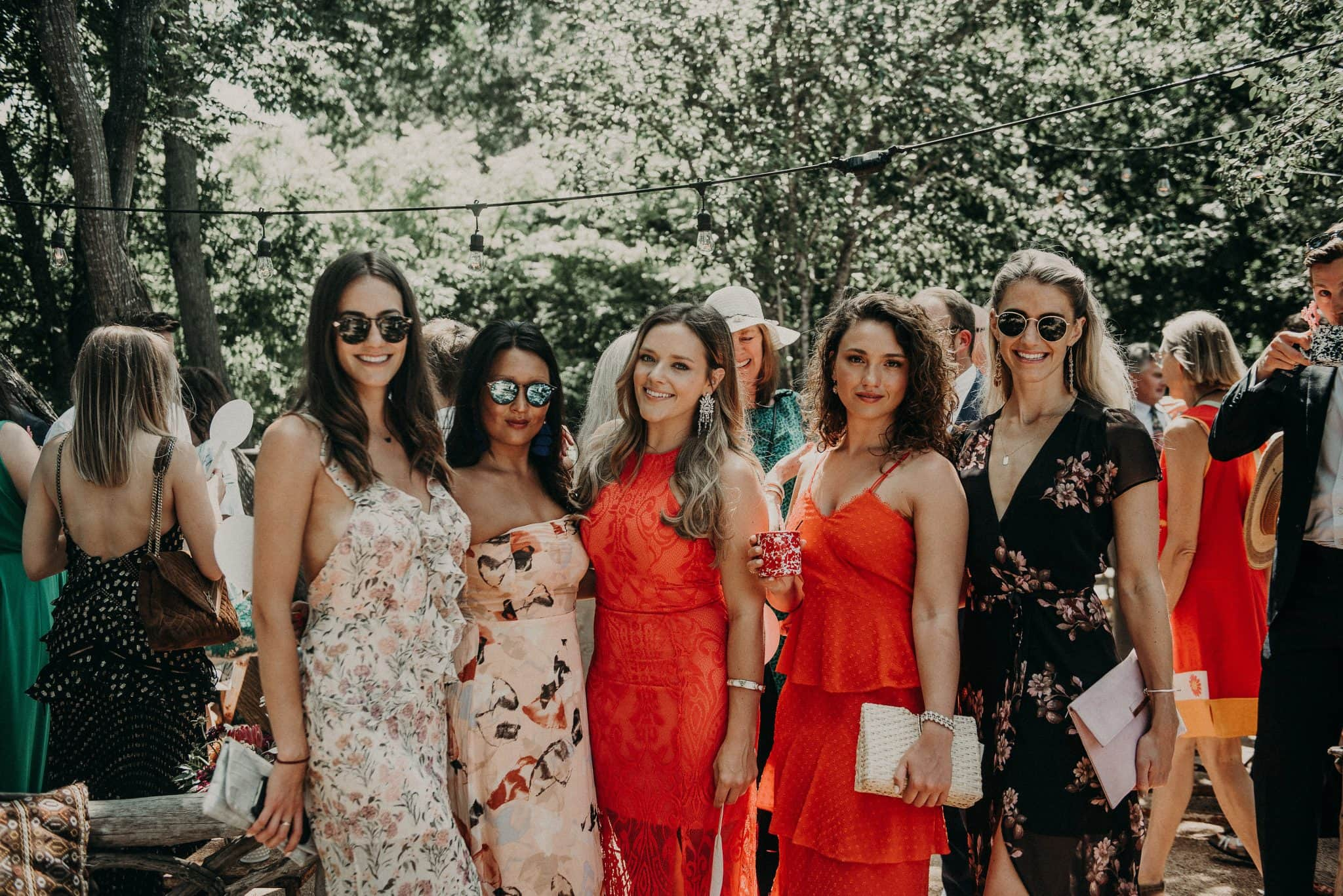 five female wedding guests standing side-by-side and smiling at the camera in Austin, Texas during the reception and with other wedding guests mingling behind them