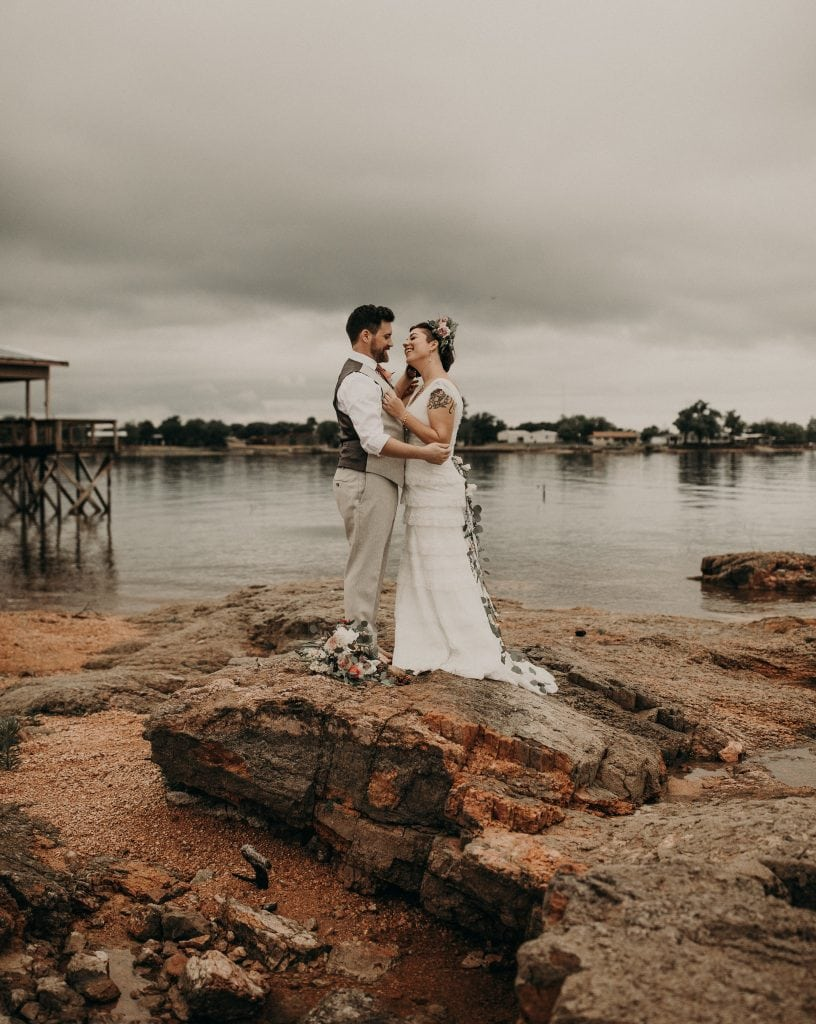 Bride and groom stand face-to-face smiling at each other with their arms around each other on a giant rock in front of Lake Buchanan in Texas. Photograph by Austin, Texas wedding photographer Nikk Nguyen.