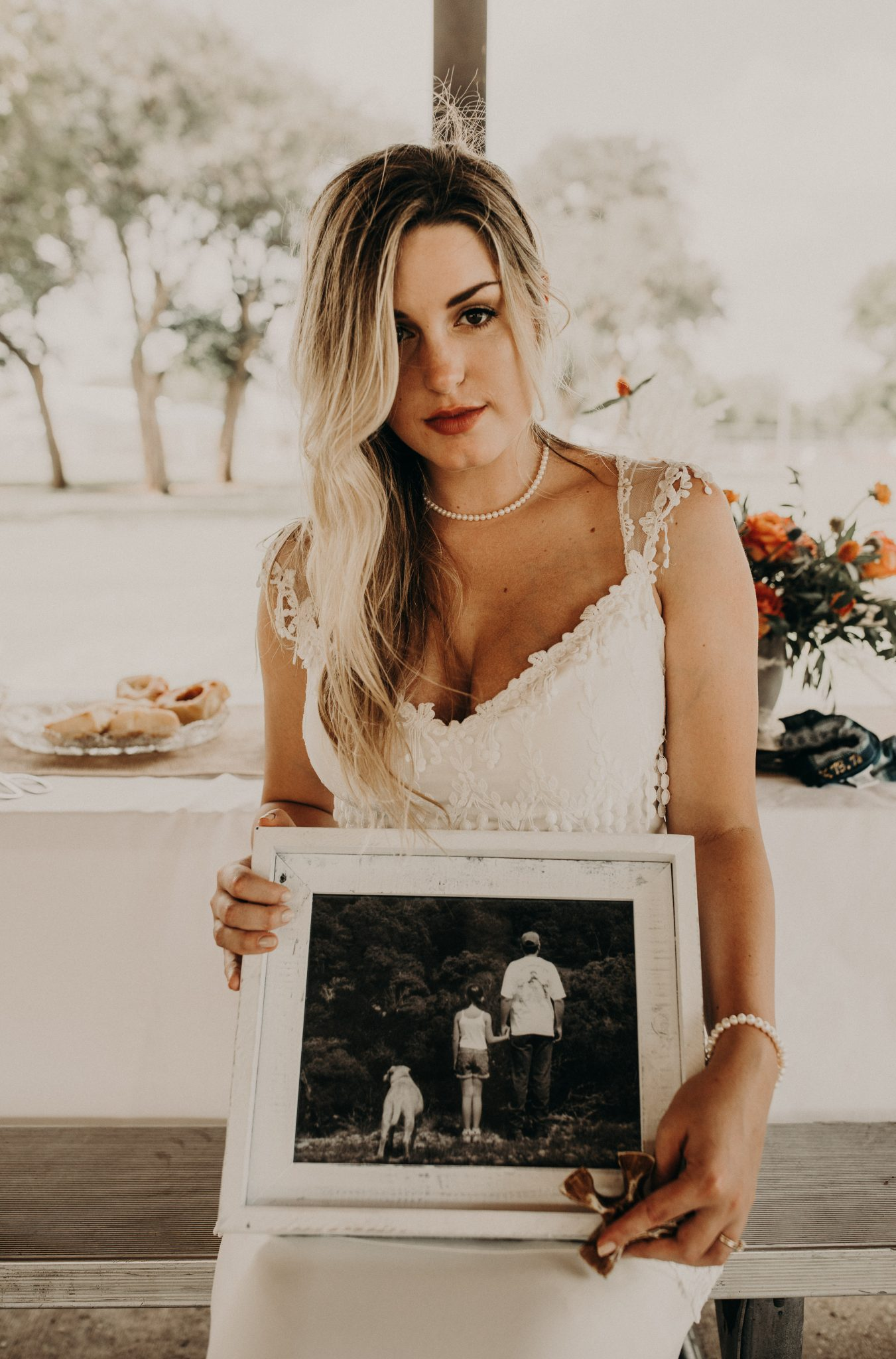 bride sitting on a wooden bench and holding a photograph in a white wooden frame of a dog and a small girl holding an adult male's hand. behind the bride is a table with a plate of donuts and flowers on it and the table is covered in a white tablecloth