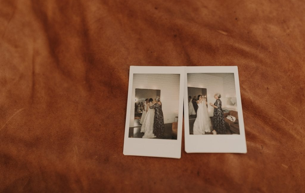 against a leather background are two small polaroid photos of the bride with her mother getting ready for the wedding