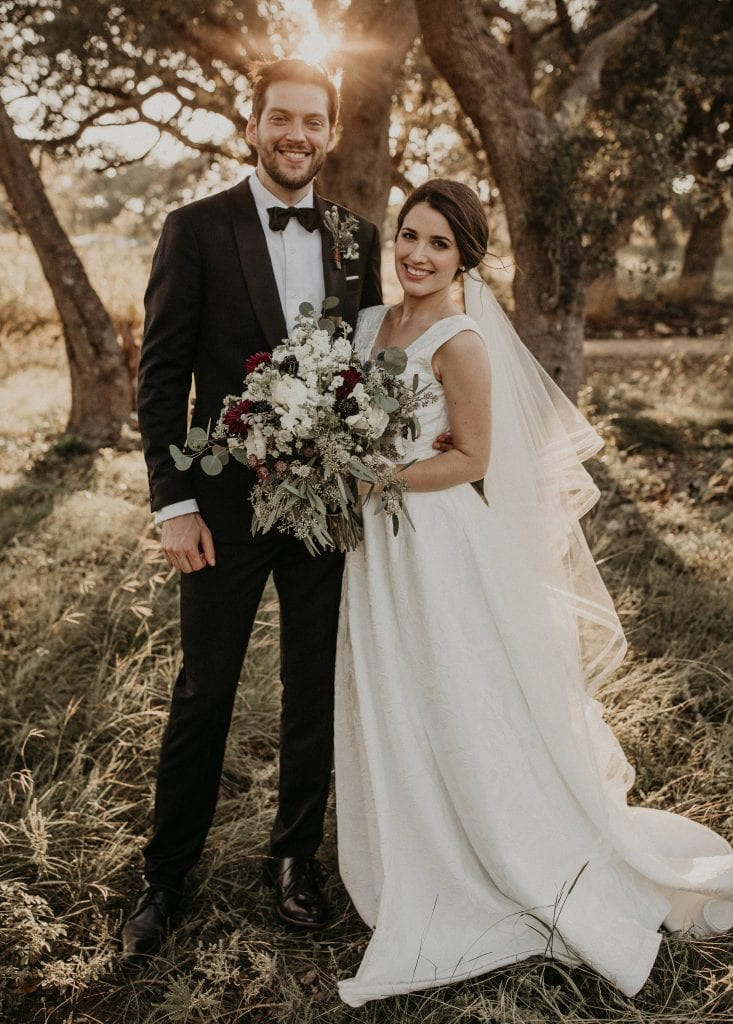 Bride holds her bouquet as she stands with the groom facing the camera and smiling in the grass with trees and the sunset behind them at Prospect House in Dripping Springs, Texas. Photograph by Austin, Texas wedding photographer Nikk Nguyen.