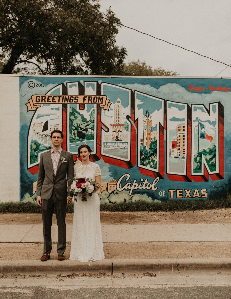 "Bride holding her bouquet with her left hand and holding the grooms hand on her right as they stand next to each other in front of the painted wall that says ""greetings from Austin capitol of Texas"" in Austin, Texas. Photograph by Austin, Texas wedding photographer Nikk Nguyen."