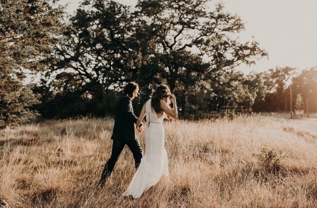 Bride and groom holding hands as they walk across a field of tall grass toward the sunset at LaLa Park in San Marcos, Texas. Photograph by Austin, Texas wedding photographer Nikk Nguyen.