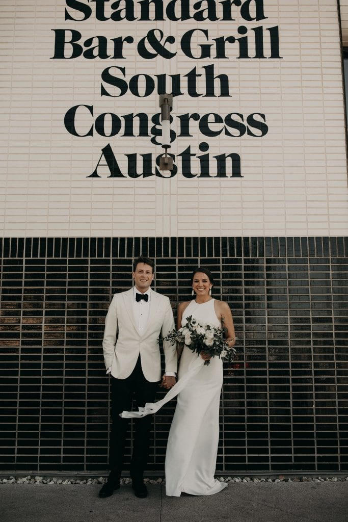 "Bride and groom holding hands while the bride holds her bouquet as they stand in front of a black and white tile wall that says ""Standard Bar & Grill South Congress Austin"" in downtown Austin, Texas. Photograph by Austin, Texas wedding photographer Nikk Nguyen."