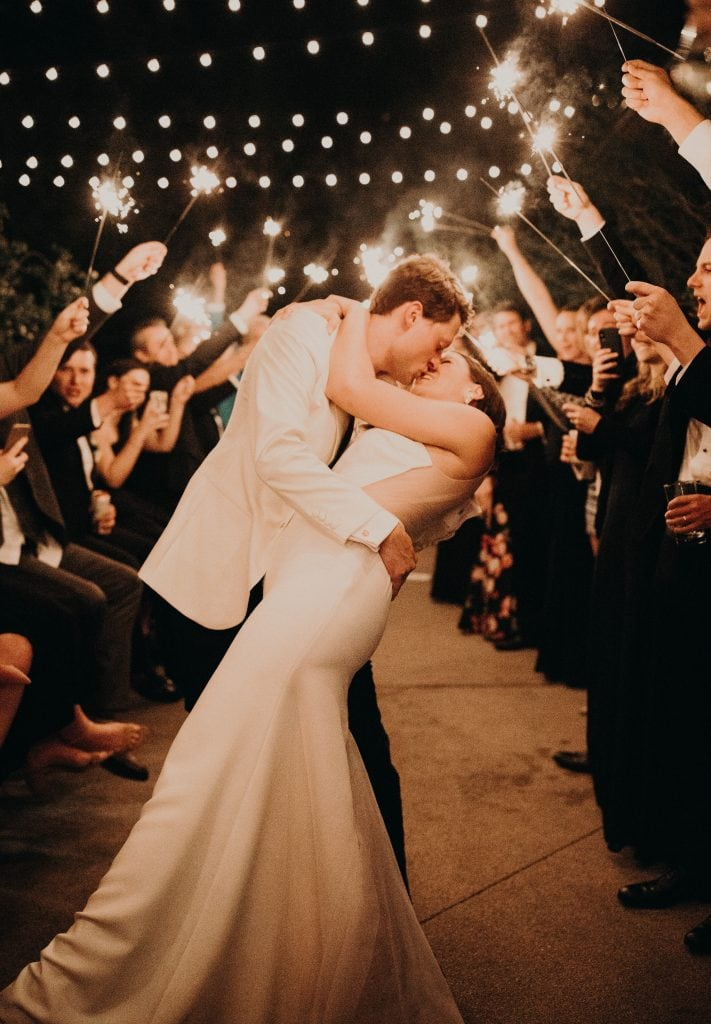 groom holding the bride as he leans her back to kiss her while exiting and the wedding guests are holding up sparklers in downtown Austin, Texas