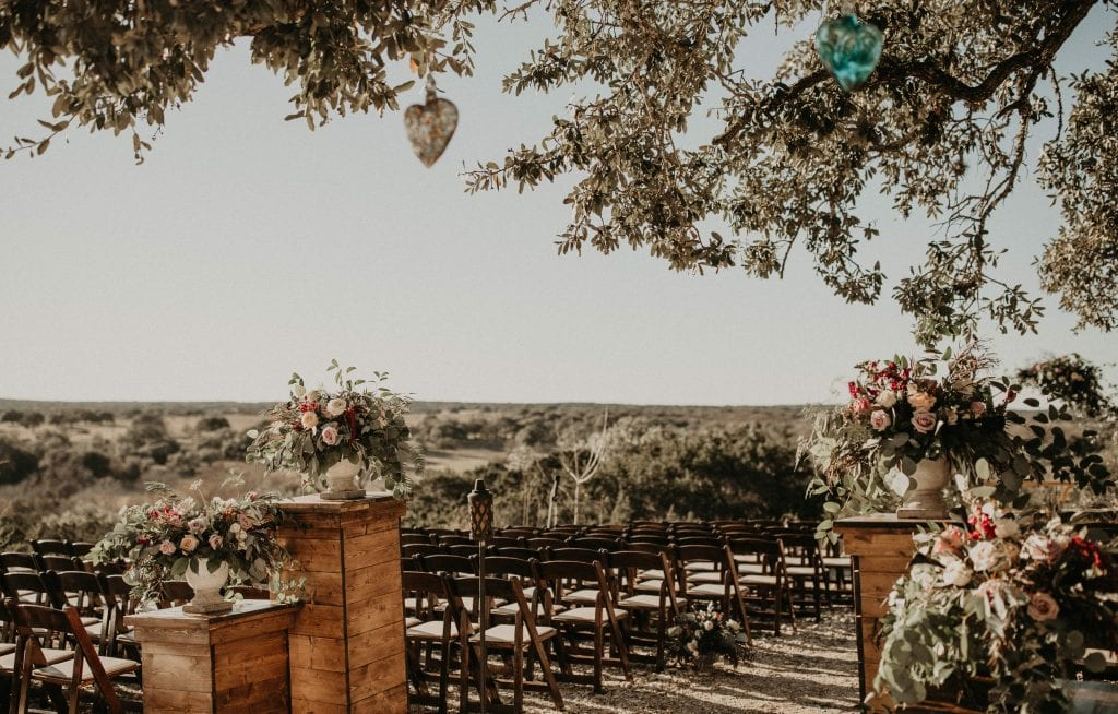 Ceremony set up of wooden chairs and ornate floral designs at Villa at Manzuelo Vineyards in Austin, Texas. Photograph by Austin, Texas wedding photographer Nikk Nguyen.