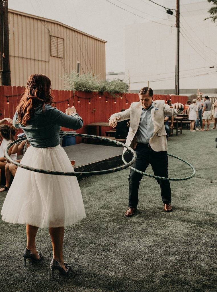 Engagement shoot photo of bride and groom to be hula hooping outside on the lawn of Little Lucy's Mini Donuts in Austin, Texas. Photograph by Austin, Texas wedding photographer Nikk Nguyen.