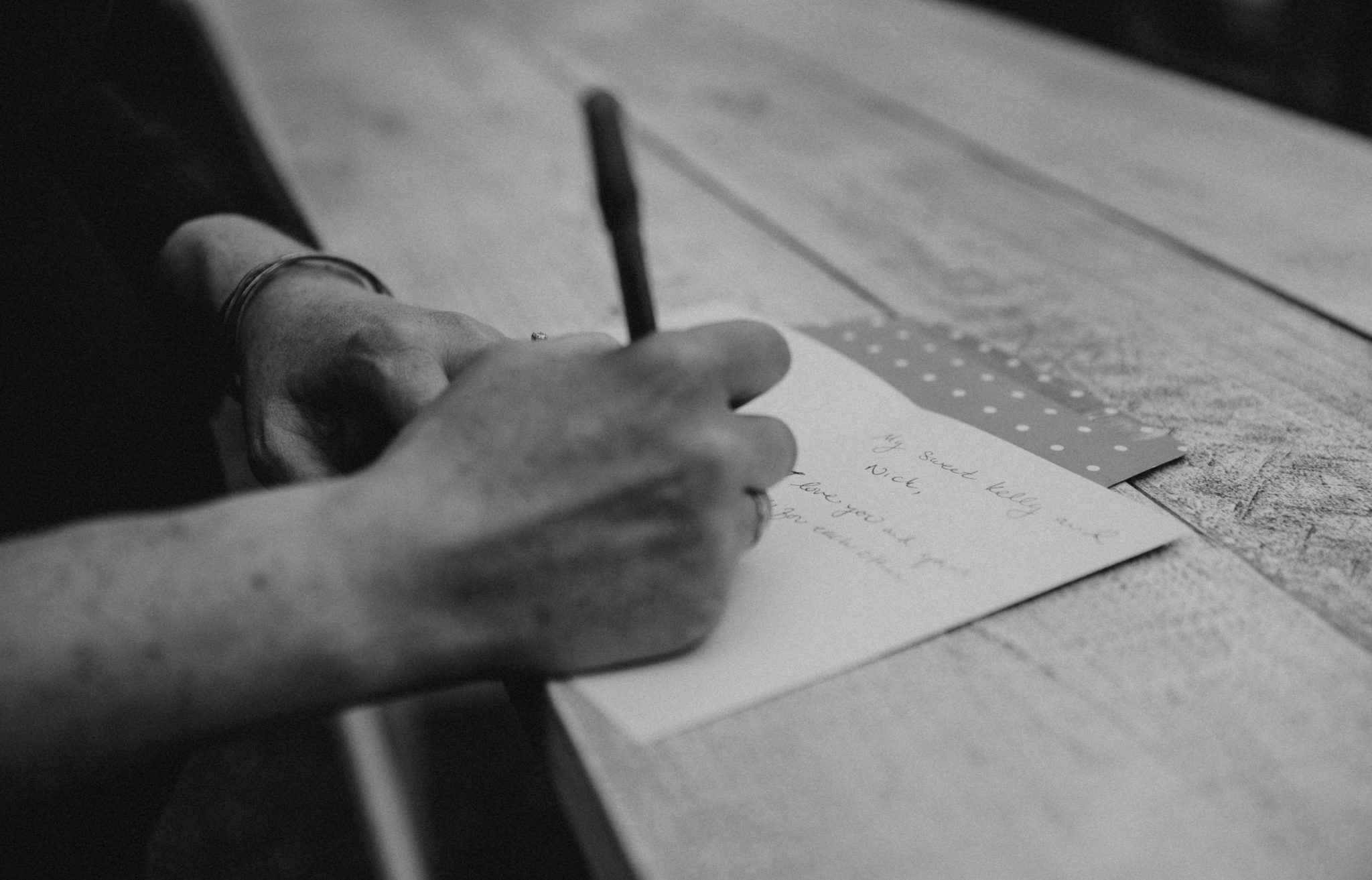 Black and white photo of a women's writing with her right hand in a card on a wooden table at Lenoir Restaurant in Austin, Texas. Photograph by Austin, Texas wedding photographer Nikk Nguyen.