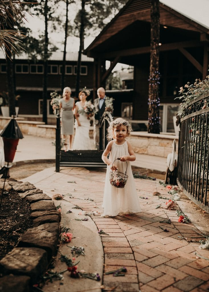 Flower girl carrying a basket of flower petals with the bride and her parents in the background at Lake Buchanan in Texas. Photograph by Austin, Texas wedding photographer Nikk Nguyen.