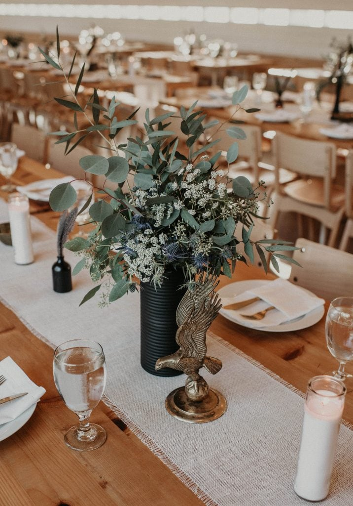Small eagle statue and floral arrangement centerpieces at Prospect House in Dripping Springs, Texas. Photograph by Austin, Texas wedding photographer Nikk Nguyen.