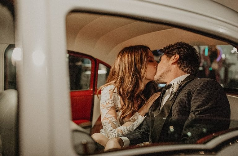 Bride and groom kiss in an old vintage Chevrolet car at the Villa at Manzuelo Vineyards in Austin, Texas. Photograph by Austin, Texas wedding photographer Nikk Nguyen.