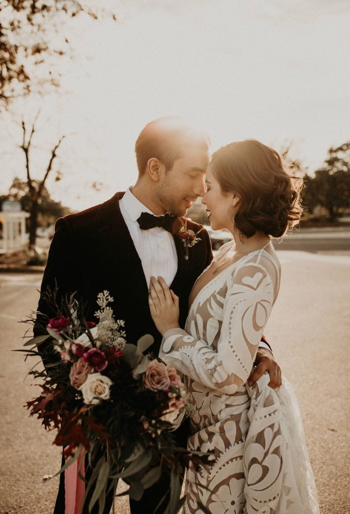 Bride and groom standing face-to-face with their foreheads touching while the groom holds the bouquet as the sunsets in the background in Austin, Texas.  Photograph by Austin, Texas wedding photographer Nikk Nguyen.
