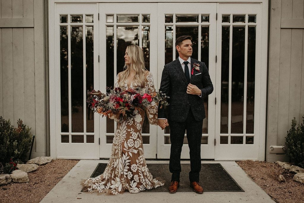 bohemian bride holds her bouquet and the groom's hand as they stand side by side in front of the barn at The Addison Grove in Austin, Texas
