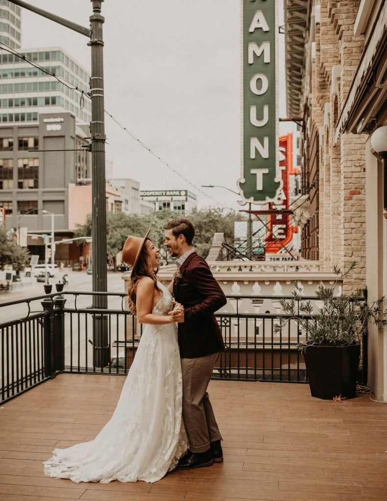 Bride and groom dance on a patio in front of urban style brick buildings in down town Austin, Texas. Photograph by Austin, Texas wedding photographer Nikk Nguyen.