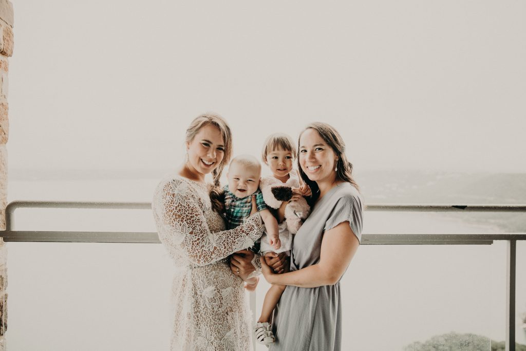 The bride and her female friend holding 2 children as they all smile at the camera and stand on a balcony overlooking a body of water.  Photograph by Austin, Texas wedding photographer Nikk Nguyen.