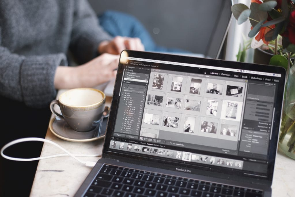 A charging laptop with photo editing software open, sitting on a counter with a female on her laptop and a latte in the background.