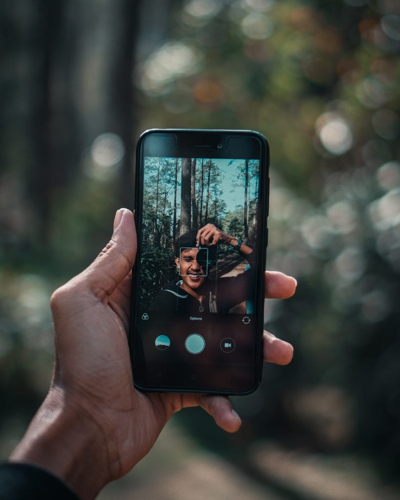 Picture of a young man holding an iPhone and taking a selfie of himself as he takes a photo with his camera with a forest behind him