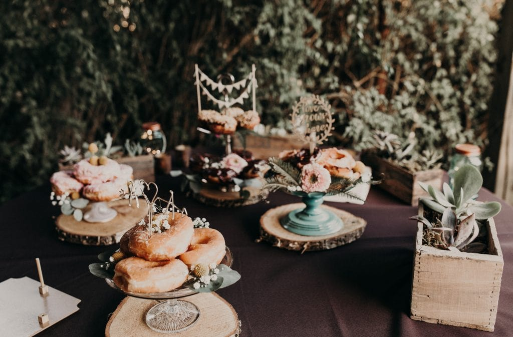 Dessert table with a spread of donuts on serving platters surrounded by succulents. Photograph by Austin, Texas wedding photographer Nikk Nguyen.