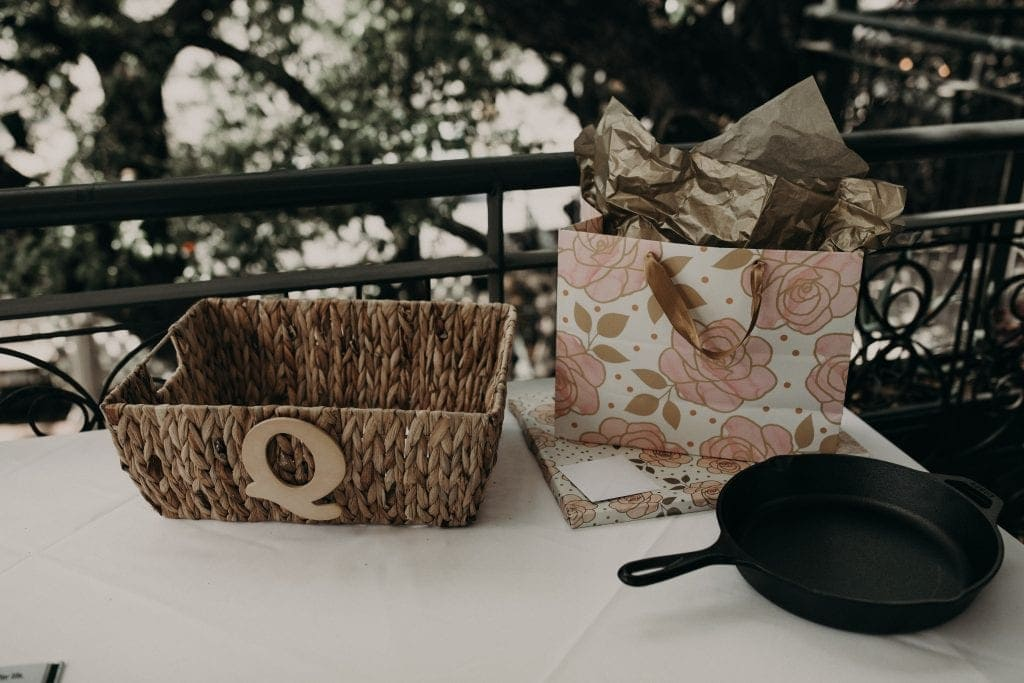 a gifts table with a basket, a gift bag with a matching wrapped gift, and a skillet