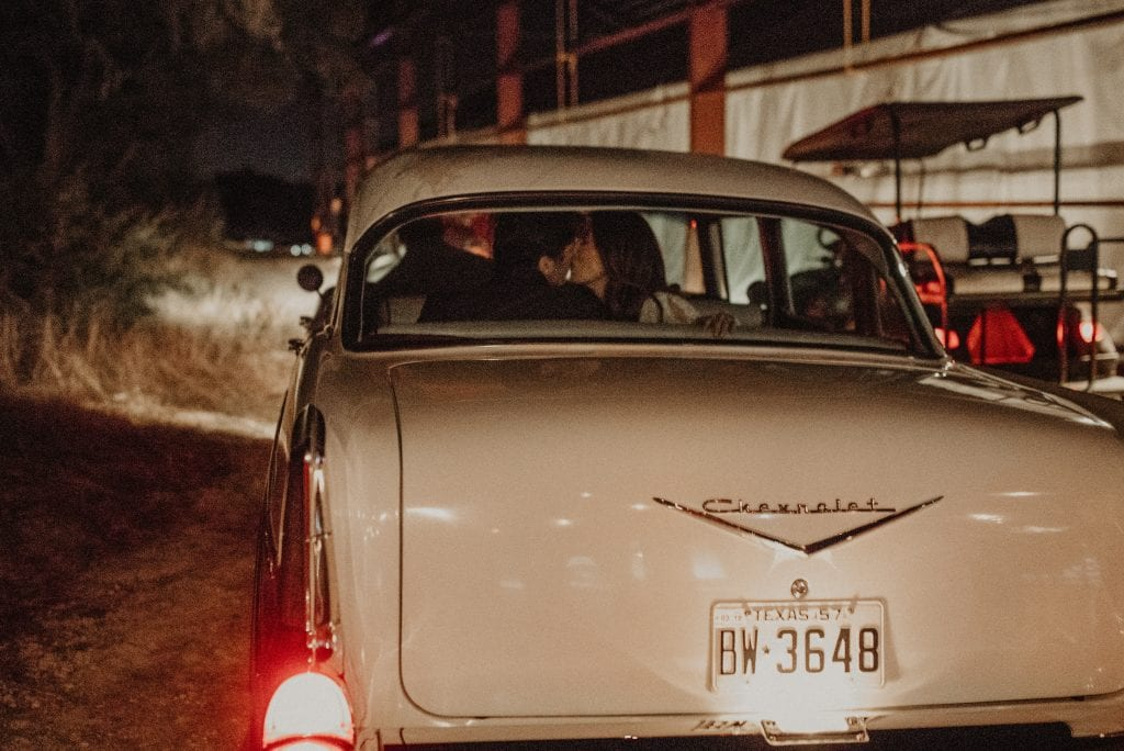 Photograph from behind a vintage Chevrolet car where the bride and groom are kissing in the back seat at Villa at Manzuelo Vineyards in Austin, Texas. Photograph by Austin, Texas wedding photographer Nikk Nguyen.
