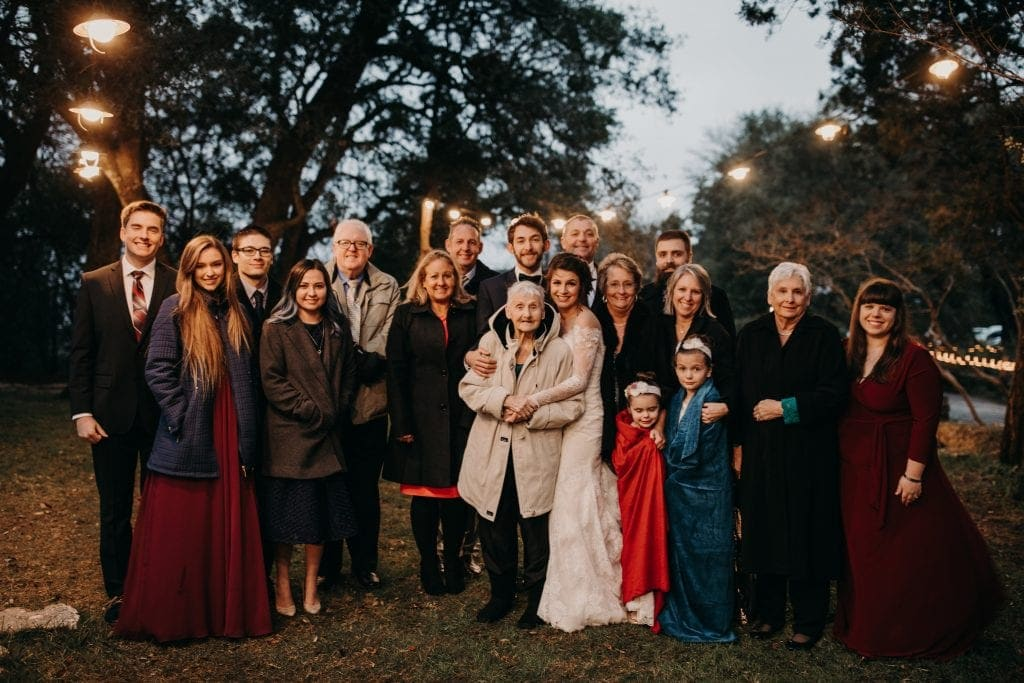 Bride and groom pose with wedding guests of all ages on the lawn at House on the Hill in Austin, Texas. Photograph by Austin, Texas wedding photographer Nikk Nguyen.