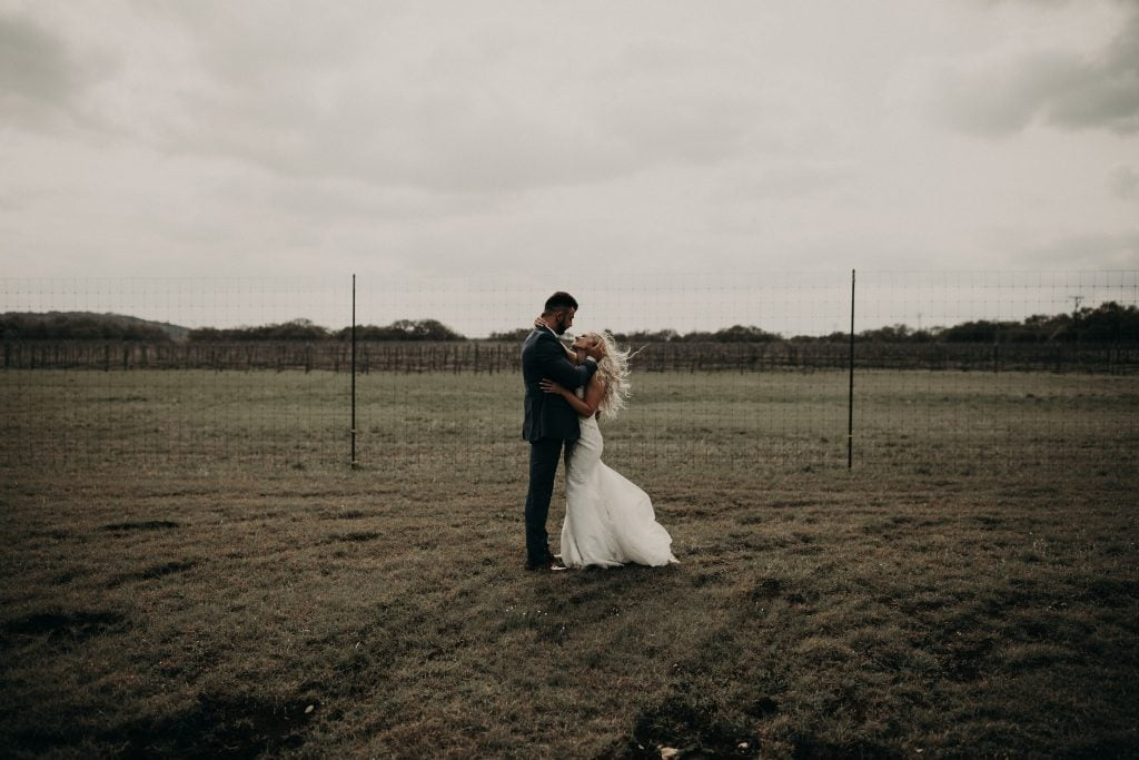Bride and groom embracing in a field in Austin, Texas. Photograph by Austin, Texas wedding photographer Nikk Nguyen.