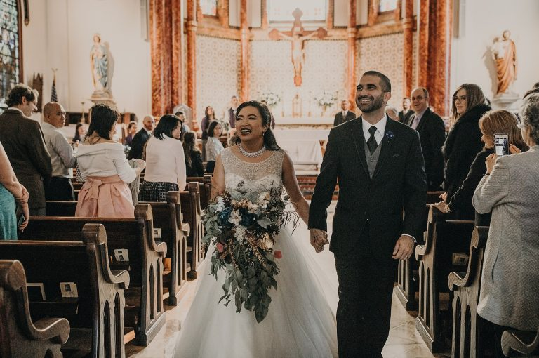 Bride and groom smiling as they hold hands and walk down the aisle after their ceremony at St Mary Cathedral in downtown Austin, Texas. Photograph by Austin, TX wedding photographer NIkk Nguyen.