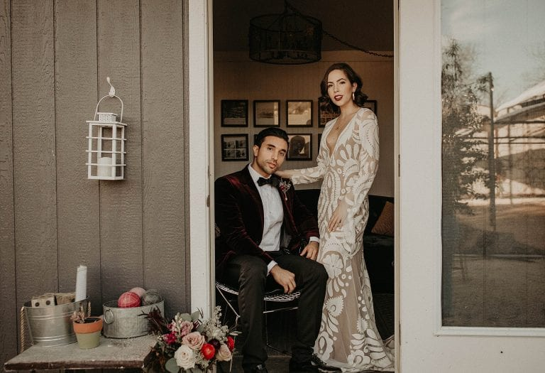 elegant bohemian bride stands next to groom as he sits in a chair in the doorway of a small house at The Addison Gove in Austin, Texas