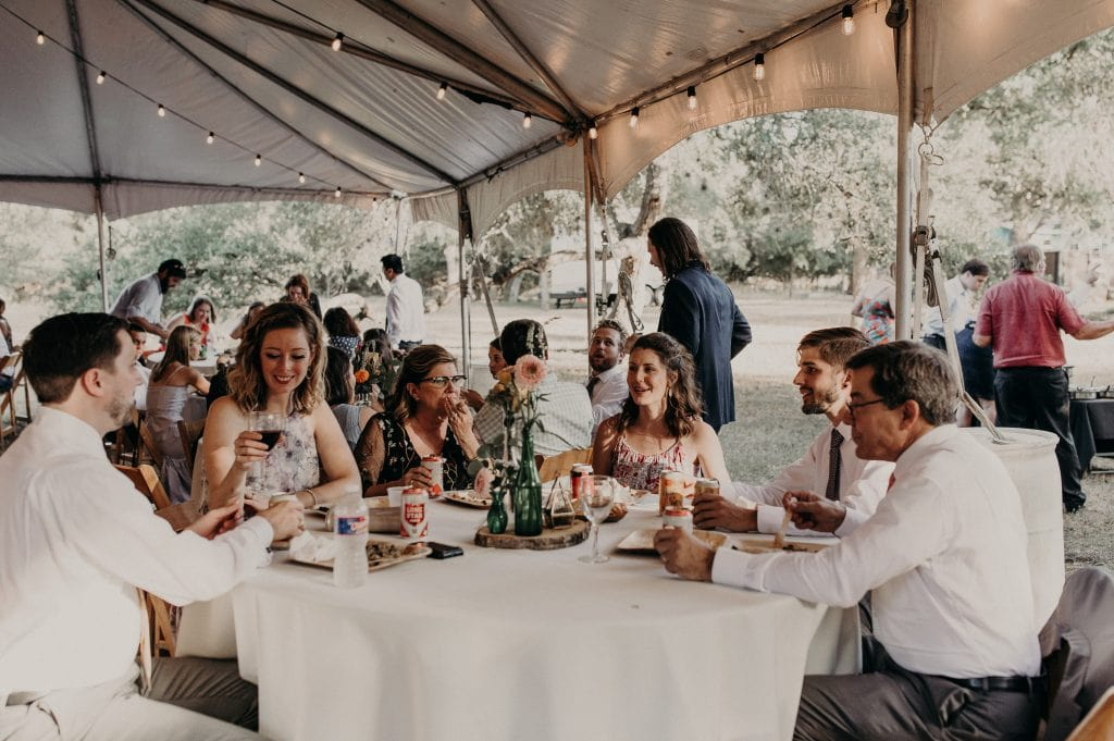 Wedding guests at a table enjoying their meal and each other's company at LaLa Park in San Marcos, Texas. Photograph by Austin, Texas wedding photographer Nikk Nguyen.
