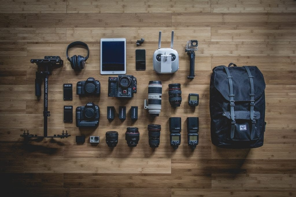 A bird's eye view of photography gear including a tripod, headphones, memory cards, iPad, lenses, flashes, and a backpack arranged neatly on a hardwood floor