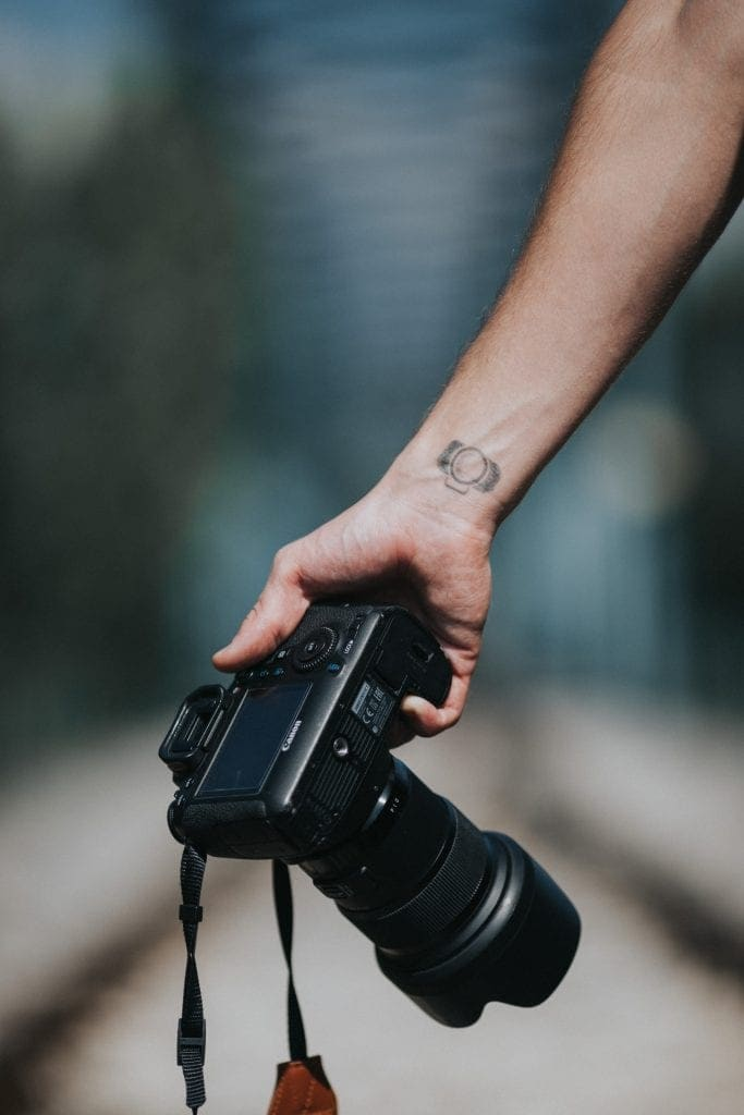 A young mans arm from below the elbow with a tattoo of a camera on his wrist holding a camera with an extended lens and a strap.