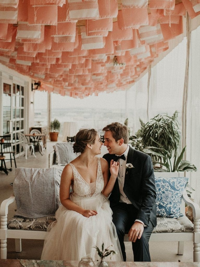 bride and groom sit facing and smiling at each other on a bench on the decorated balcony at The LINE Hotel in Austin, Texas