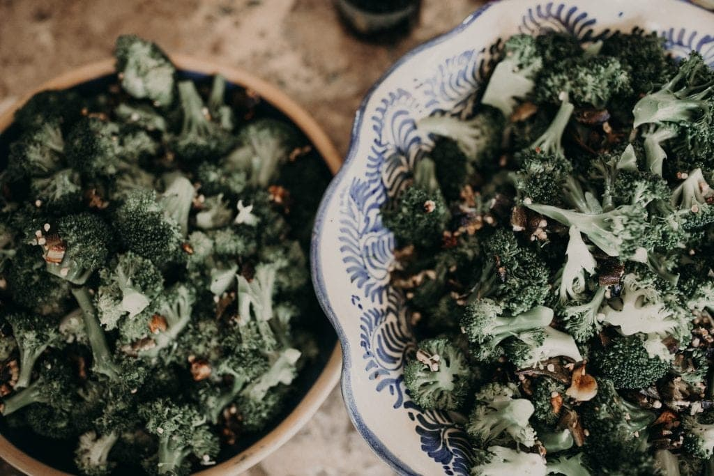 2 bowls of broccoli topped with a handful of nuts. Photograph by Austin, Texas wedding photographer Nikk Nguyen.