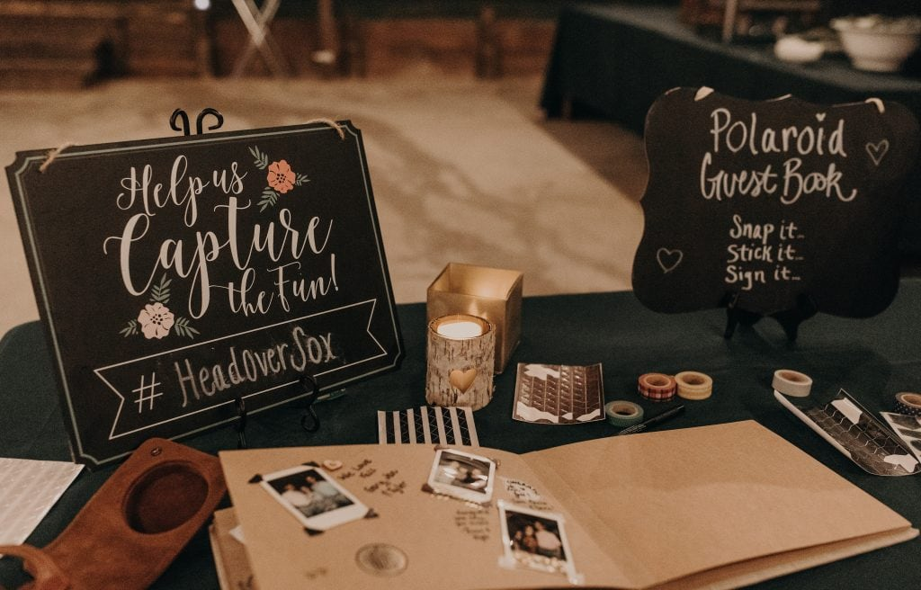 "Wedding guest book table with a wedding guest book and two black chalkboard signs that say ""Help us capture the fun #headoversox"" and ""polaroid guest book. snap it. stick it. sign it."" Photograph by Austin, Texas wedding photographer Nikk Nguyen."