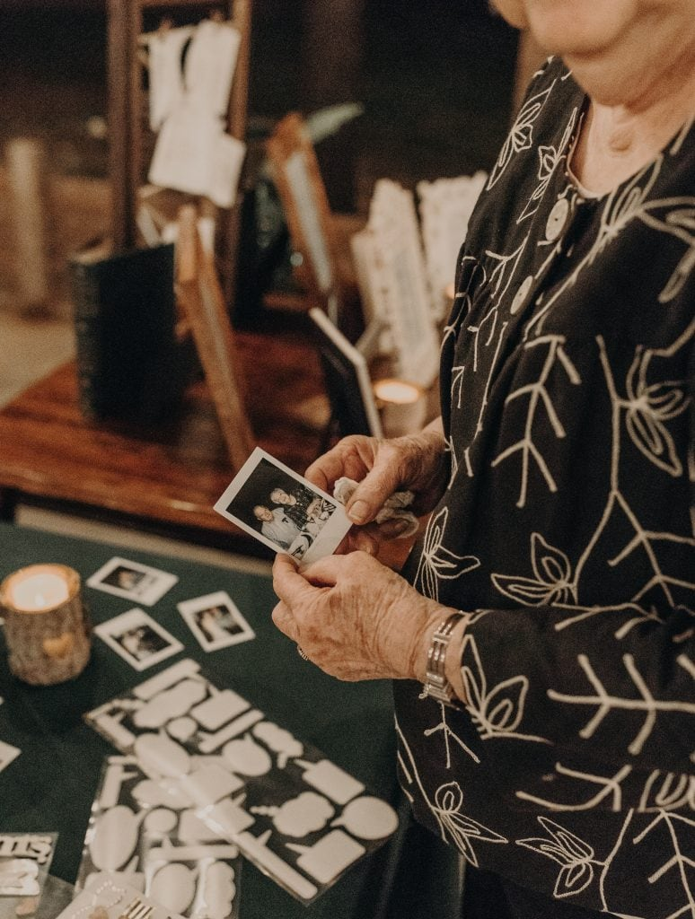 Older woman holding a small polaroid photo of her and a man while standing in front of a wedding guest book table. Photograph by Austin, Texas wedding photographer Nikk Nguyen.