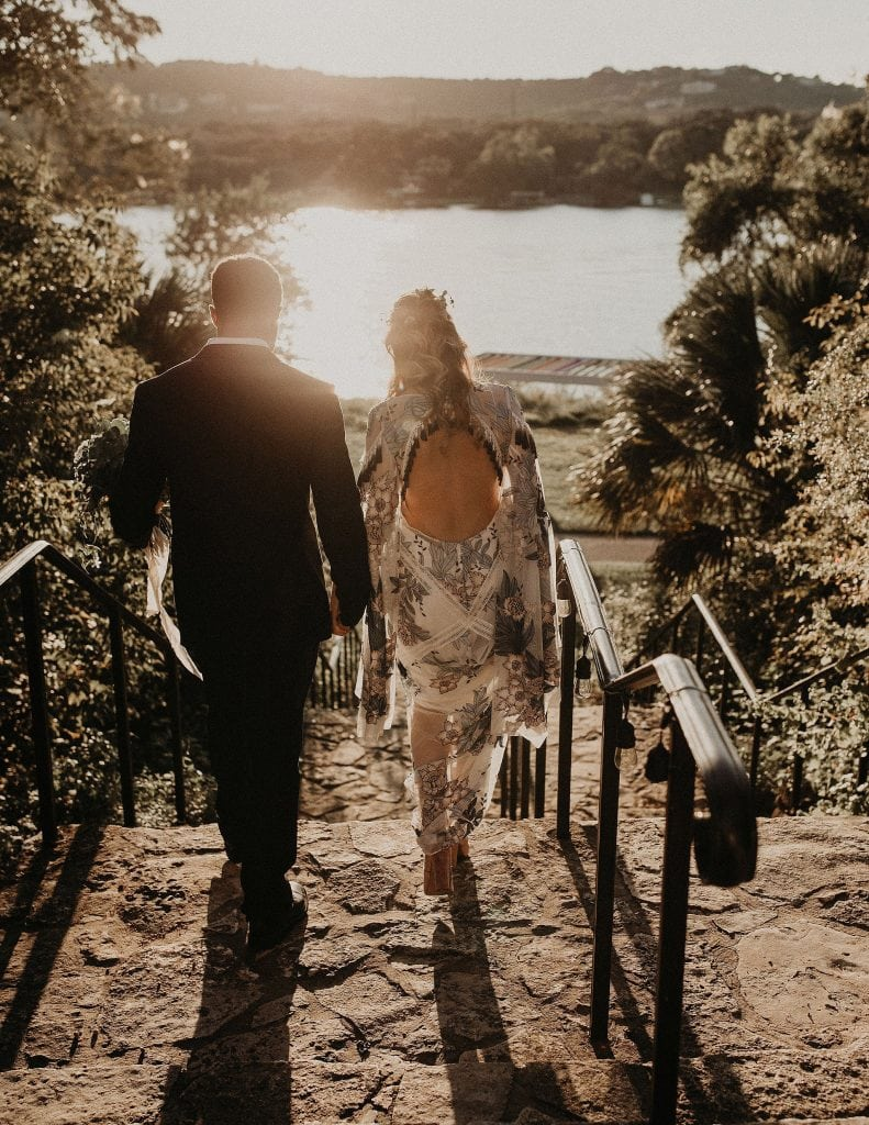 A shot from behind a bride and groom holding hands as they approach a stone staircase leading to a lake with the sun setting over it in Laguna Gloria in Austin, Texas. Photograph by Austin, Texas wedding photographer Nikk Nguyen.