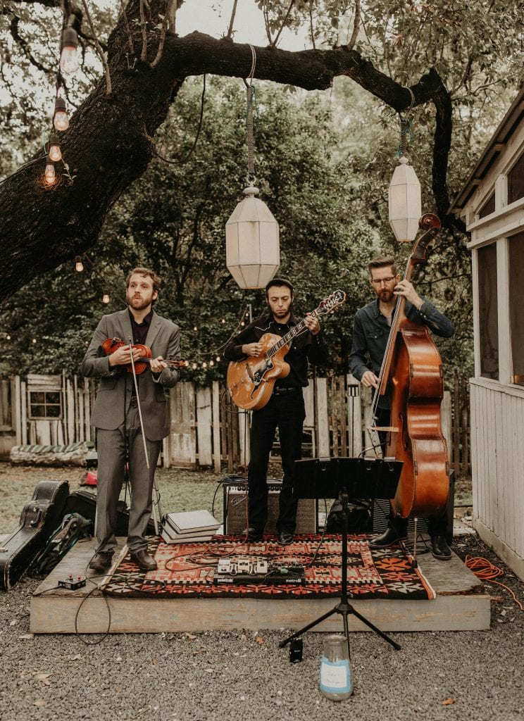 Violinist, guitar player, and cello player playing live music for an outside wedding. Photograph by Austin, Texas wedding photographer Nikk Nguyen.