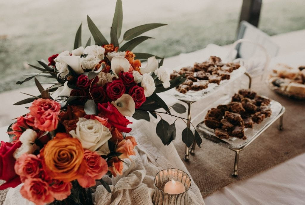 Dessert table with floral arrangements and trays of desserts. Photograph by Austin, Texas wedding photographer Nikk Nguyen.