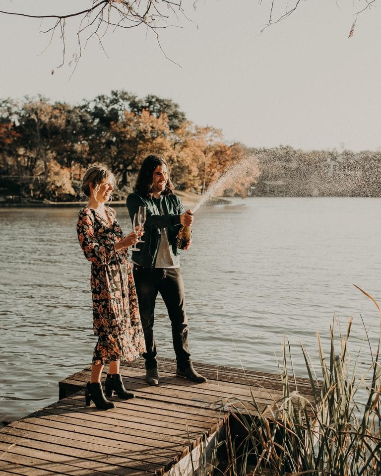 Bride to be and groom to be smile as the groom to be opens a bottle of champagne that explodes as they stand on the dock on the lake of The Contemporary Austin - Laguna Gloria in Austin, Texas. Photograph by Austin, Texas wedding photographer Nikk Nguyen.