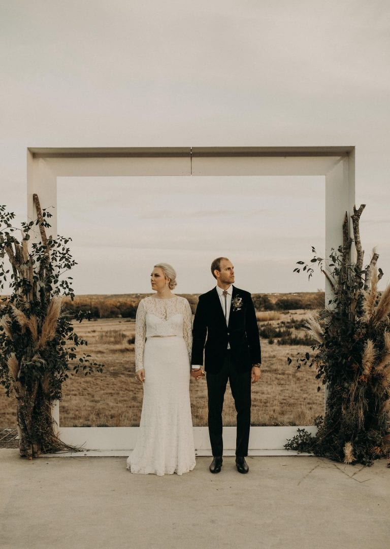 bride and groom standing side-by-side while holding hands and facing opposite directions at the decorated archway altar outside of Prospect House in Dripping Springs, Texas