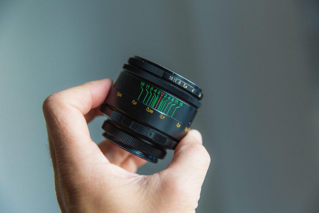 A hand holding a camera lens.