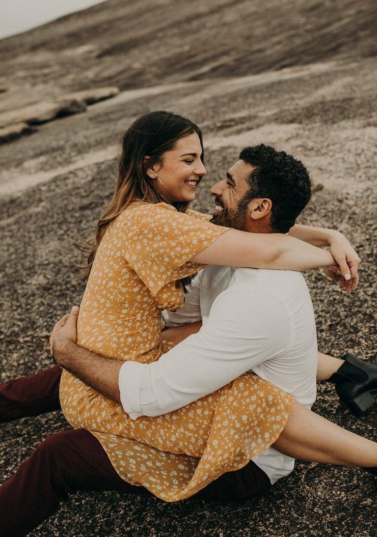 Bride to be sits on groom to be's lap while facing each other, about to kiss, with arms wrapped around each other at Enchanted rock in Fredericksburg, Texas. Photograph by Austin, Texas wedding photographer Nikk Nguyen.