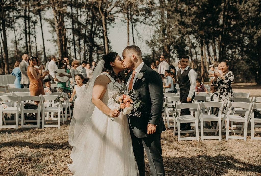 Bride and groom kiss after wedding ceremony as guests look on in the background. Photograph by Austin, Texas wedding photographer Nikk Nguyen.