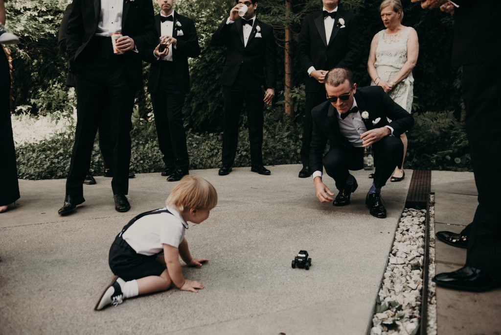 Members of the wedding party stand around as a little boy plays with a toy truck with a groomsmen who is squatting and holding a drink. Photograph by Austin, Texas wedding photographer Nikk Nguyen.